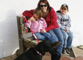 Photo of Ava sitting with her mom, brother, and companion, BoJangles