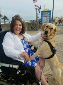 woman and her service dog on the board walk