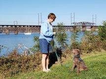 older woman and her service dog in front of a river