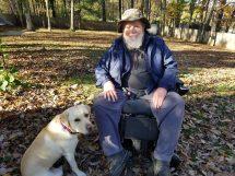 older man in wheelchair next to his service dog